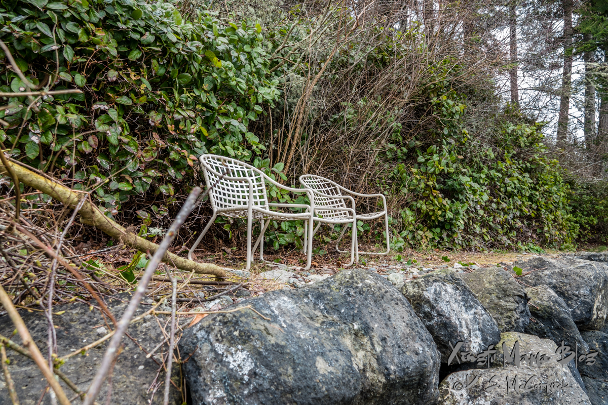 Two rather beat up lawn chairs on a stone bulkhead.