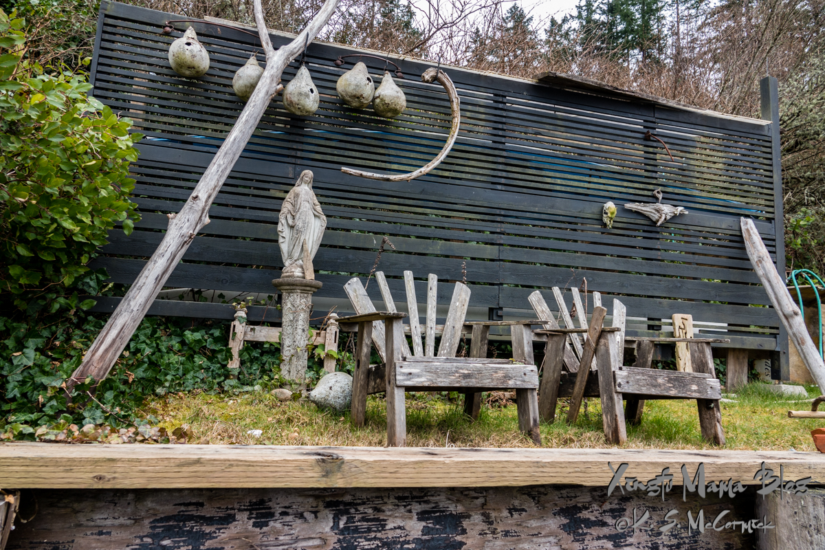 Two weathered wooden chairs, sitting on a wooden bulkhead, watched over by a statue of a saint and some gourd bird houses.
