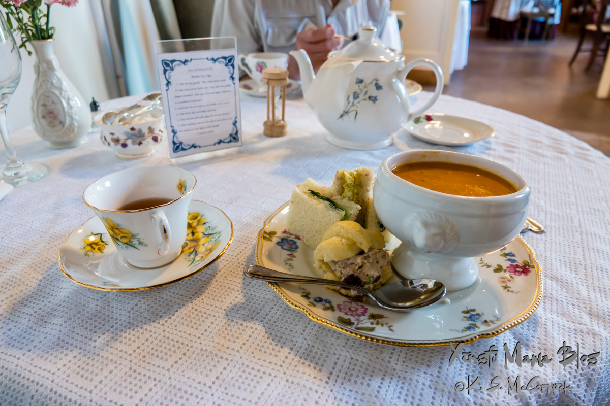 Tea cup, with tea, sandwiches and soup.