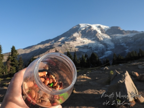 A jar of homemade trail mix with Mount Rainier in the background.