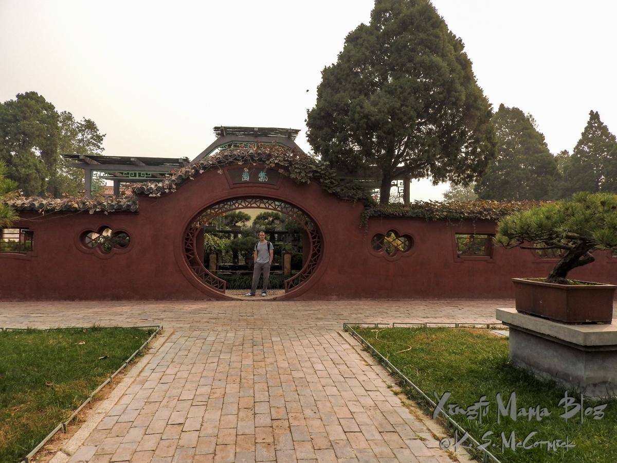Round gate into a courtyard garden in Dai Miao Temple.