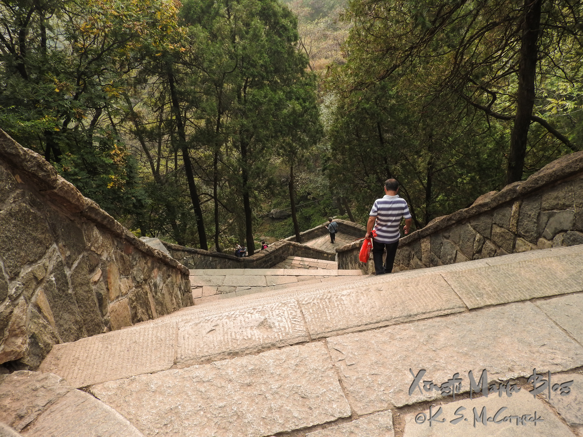 Man carrying a red bag descending steep stone steps from Mount Tai (aka Taishan) in Shandong PRovince, China.