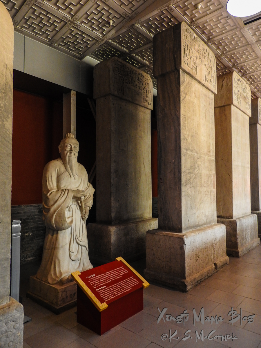 A statue tucked in amongst the steles in the hall of steles at the Confucius Temple in Beijing.