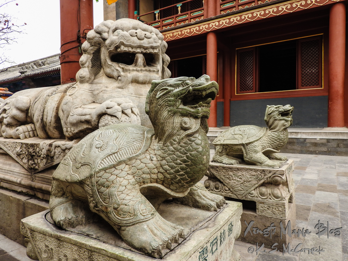 Stone statues of a lion and tortoises at the Lama Temple in Beijing.