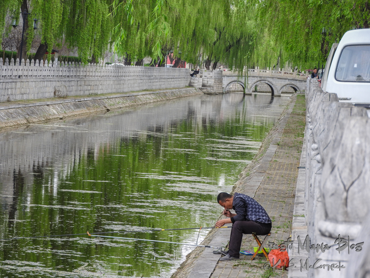 Man fishing in the mote surrounding the old city of Qufu, shandong Province, China.