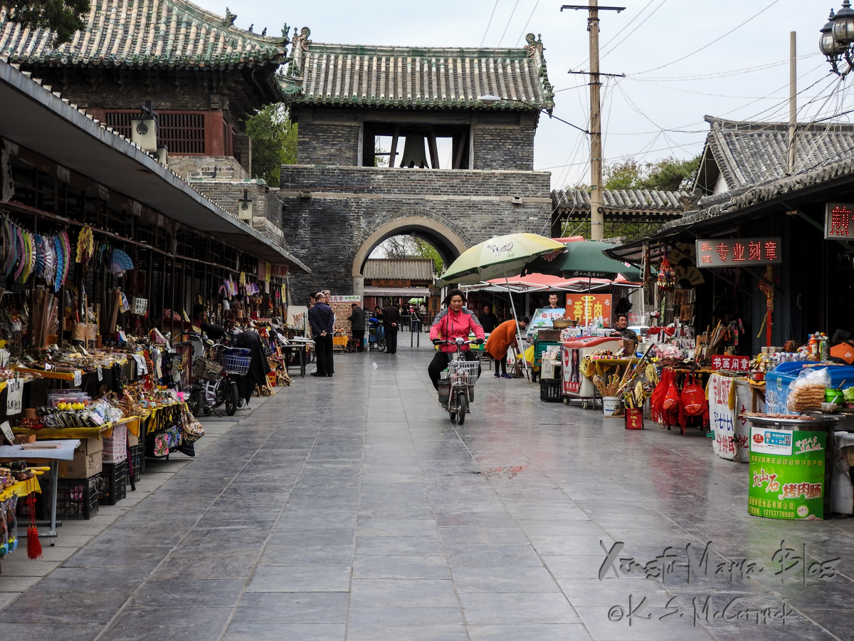 A woman riding a scooter down an empty street lined with souvenir stalls, in Qufu, Shandong Province, China.