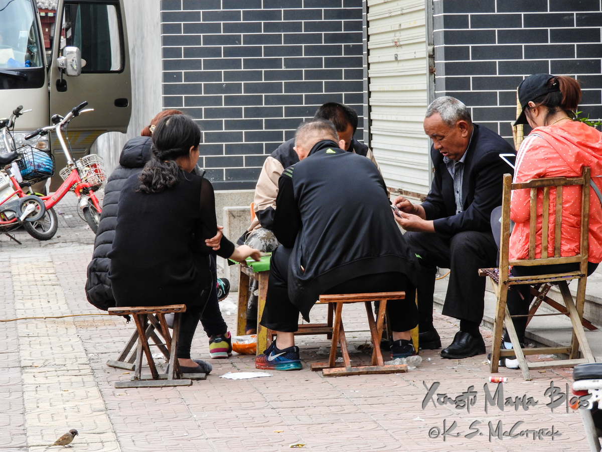Locals visiting, playing cards and checking email after the crowds have departed, in Qufu, Shandong Province, China.