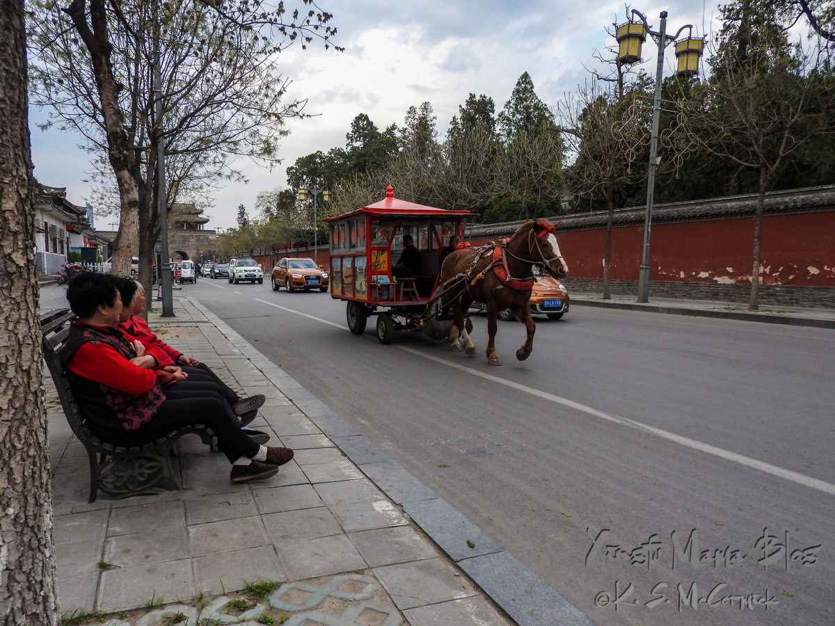 Local women watching a horse drawn carriage head down main street, probably to the stables for the night in Qufu, Shandong Province, China.