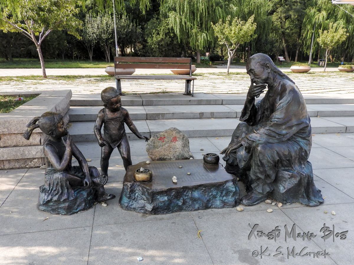 Bronze sculpture of a grandfather playing Chinese chess with children in Shouguang, China.