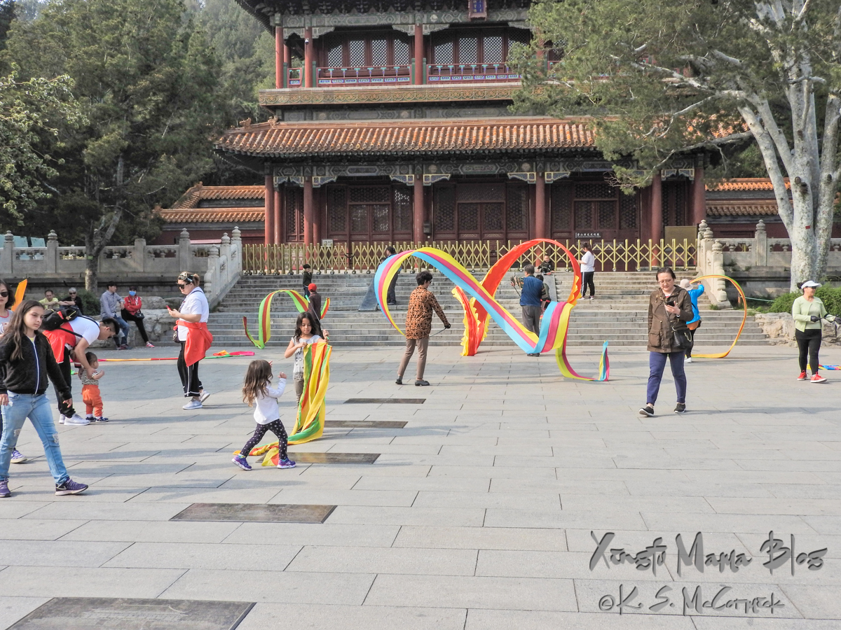 Various people using the Jing Shan Park in Beijing. Some are twirling large ribbon streamers.