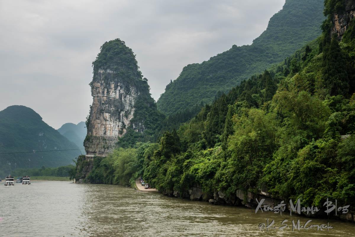 """""""Pen holder"""" karst rock pillar rises from the verdant vegetation lining the banks of the Li River. Guilin, China."""