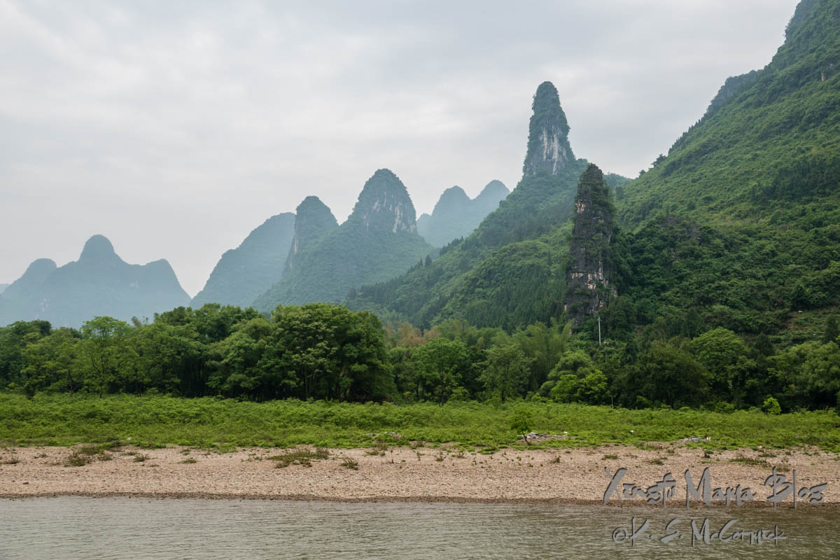 """""""Cat"""" karst formation, and others covered in verdant vegetation as the rainy season kicks in. Guilin, China."""
