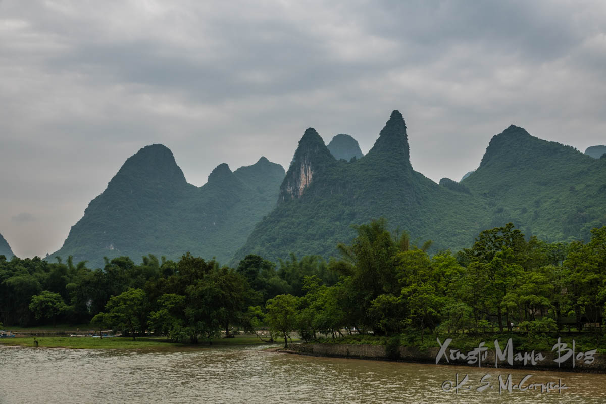 """Cat"" karst formation, and others covered in verdant vegetation as the rainy season kicks in. Guilin, China."