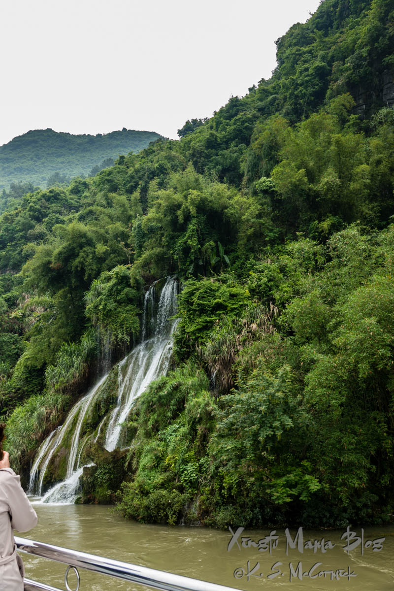Waterfall gushing out from among the verdant bamboo forest along the banks of the Li River. Guilin, China.