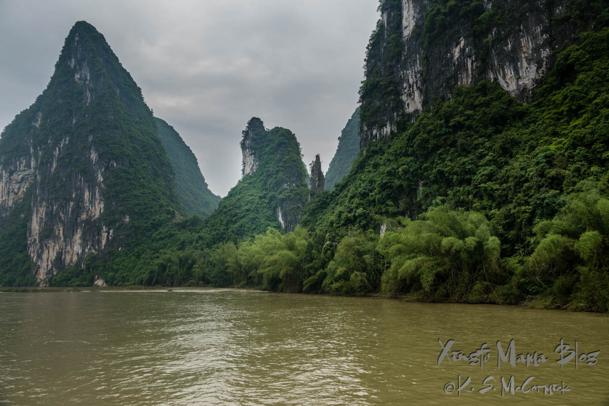 Clumps of light green bamboo and darker green of other trees and bushes growing on the karst formations along the Li River in Guilin, China.