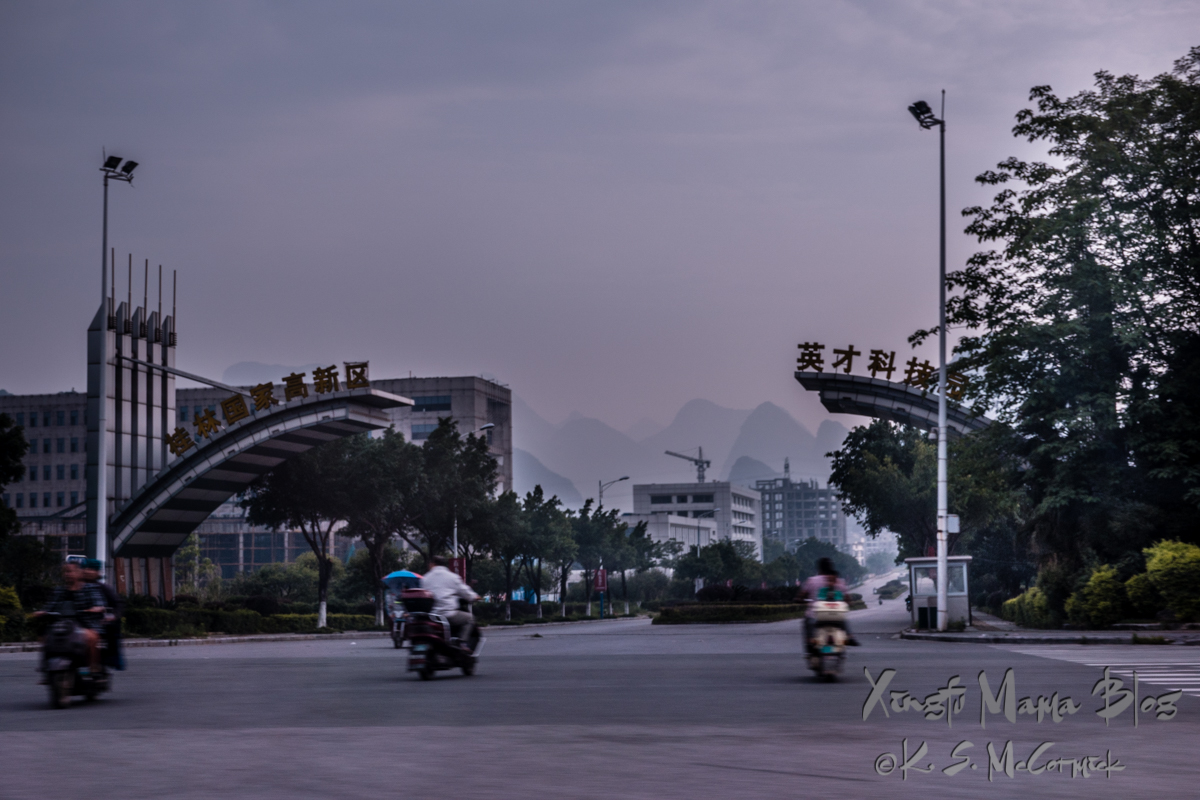 Two half arches with Chinese writing, a boulevard leading toward the karst hills visible in the distance. Guilin, China.