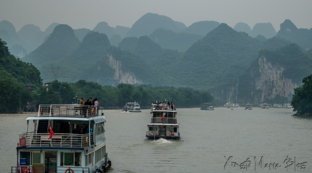 A line of boats chugging toward karst hills, on the Li River near Guilin, China.