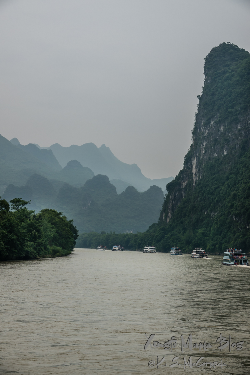 A line of tour boats passing a limestone formation on the Li River, near Guilin, China.