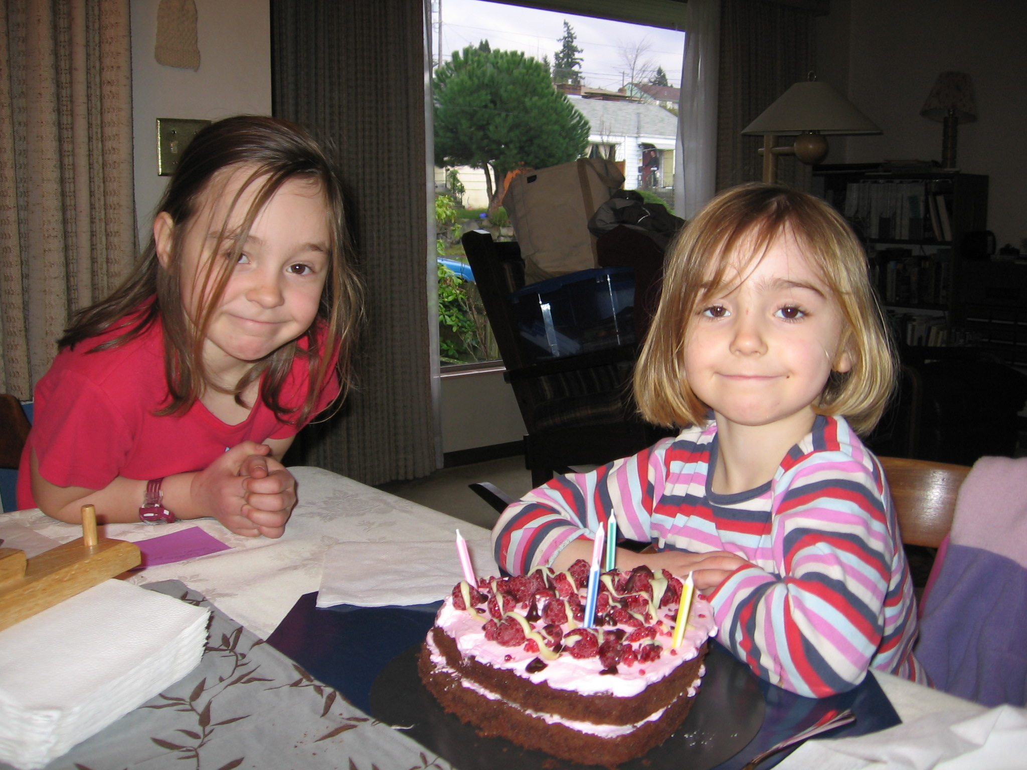 Two girls and a heart shaped birthday cake decorated with berries and five candles.