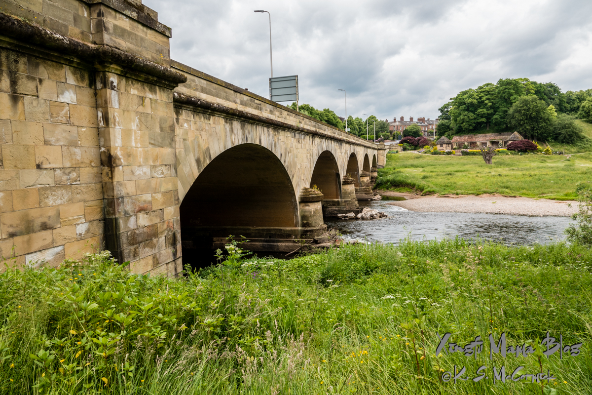 A yellow sandstone bridge with several arches crossing the Eden River in Carlisle, Cumbria, England.