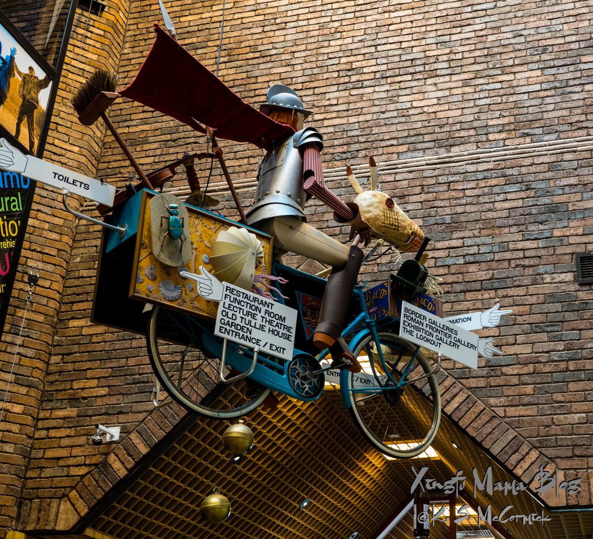 A fanciful piece of art that has an armor clad border reiver riding a bicycle/horse and other stuff machine hangs in the lobby of the Tullie House Museum, Carlisle, Cumbria, England.