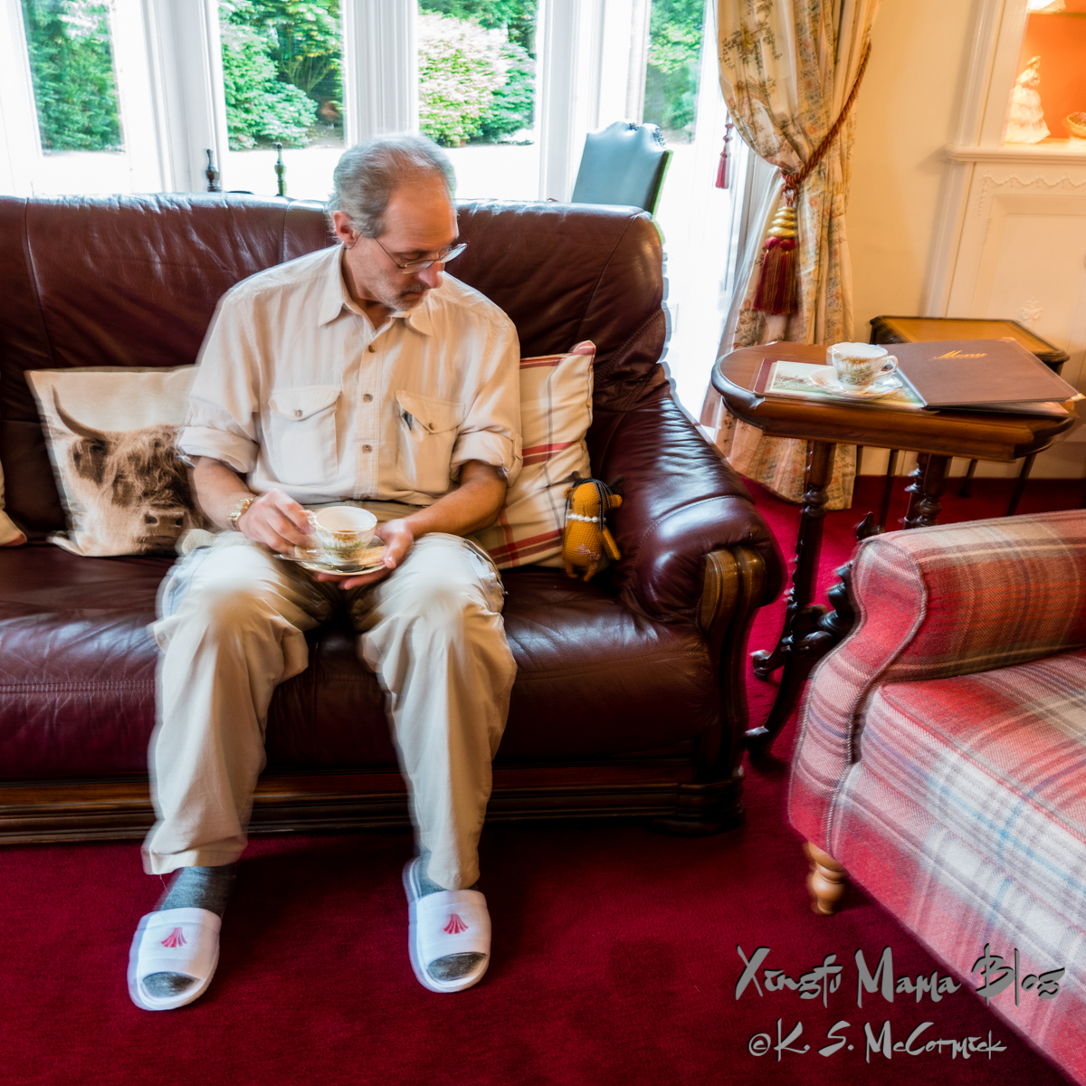 A man, drinking tea on a red leather sofa at Oakwood Park Hotel in Brampton, Cumbria, England.