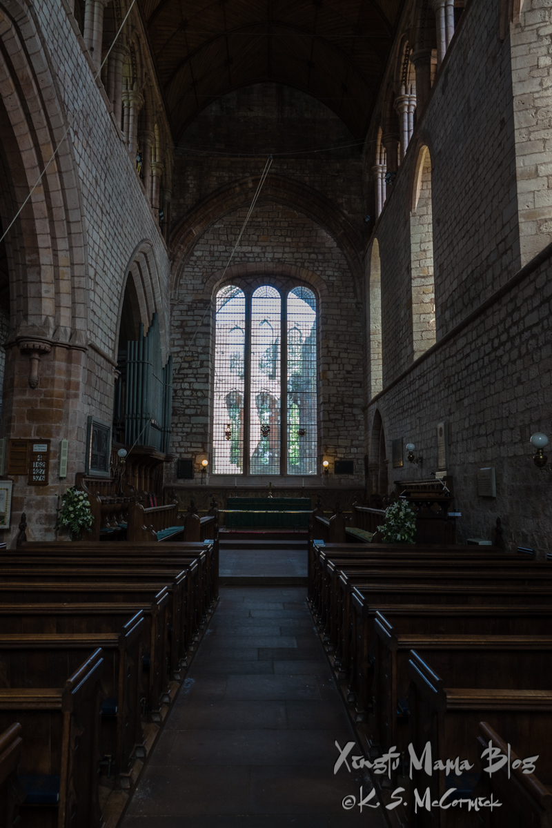 Pews in Lanercost parish church face an altar with clear windows behind it that look out to the ruins of Lanercost Abbey, Cumbria, England.