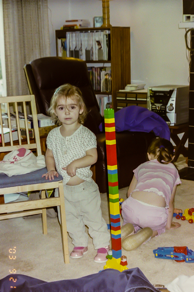 An almost three year old proud of the tower she built with duplos.