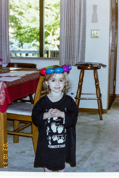 A toddler wearing a large tee shirt with Australian animal footprints with a crown made of a ring of plastic beads.