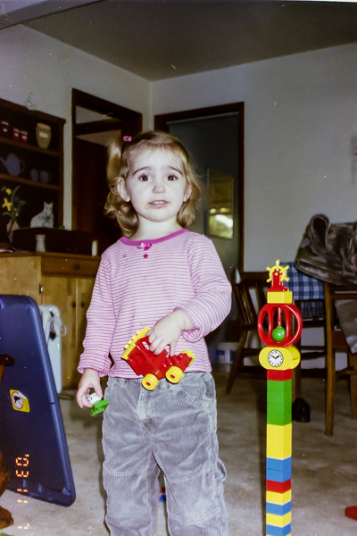 A toddler holding a Duplo car and person beside a fanciful tower she built.