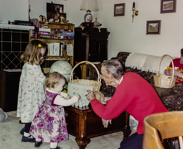 A toddler and young girl with an elderly man playing with Easter eggs.