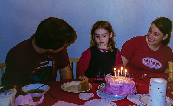 A four year old surrounded by her parents prepares to blow out the candles on the cake she helped to bake.