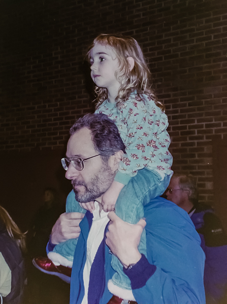A young girl sitting on the shoulders of a bearded man.