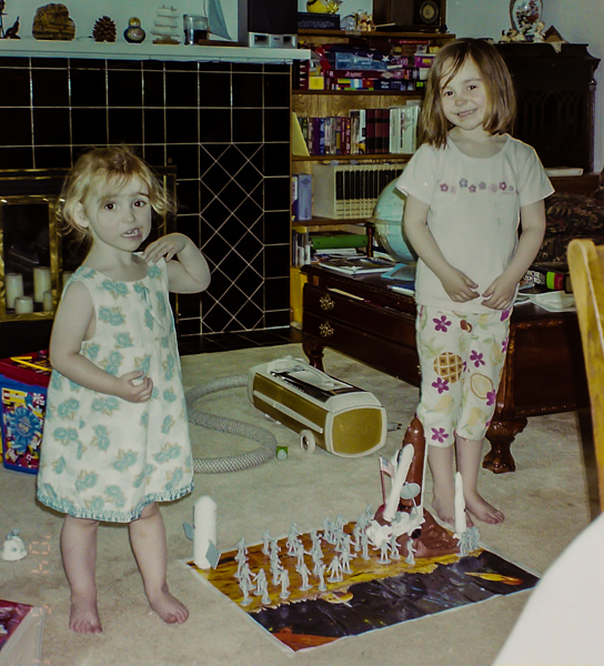 A three and six year old standing on either side of a space toy set up.