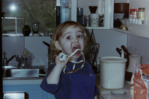 A toddler licking a beater covered with chocolate cake batter.