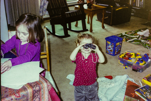 A toddler looking through binoculars. Her older sister is seriously working on a drawing.