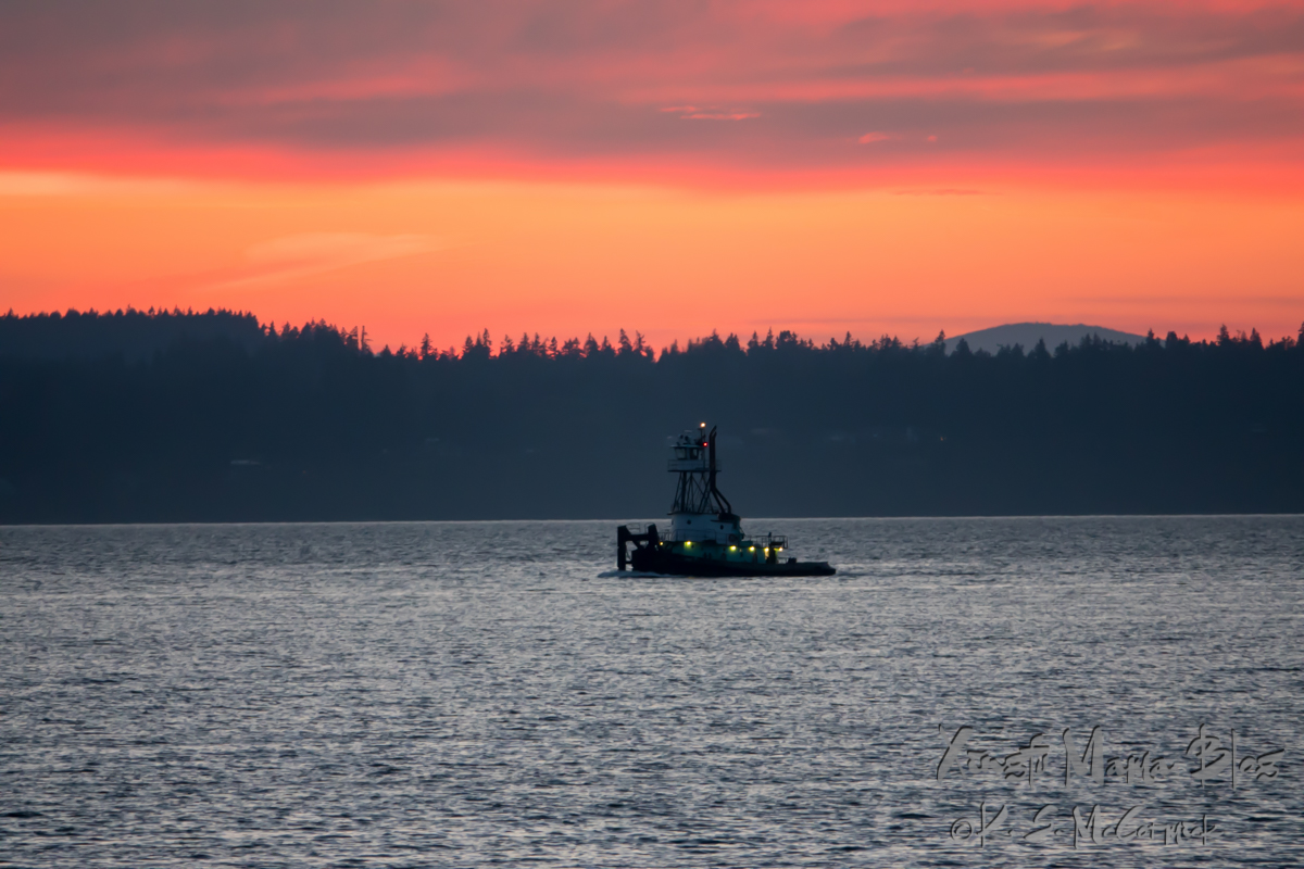 Tug boat heading out to pick up a load on Puget Sound just after sundown.