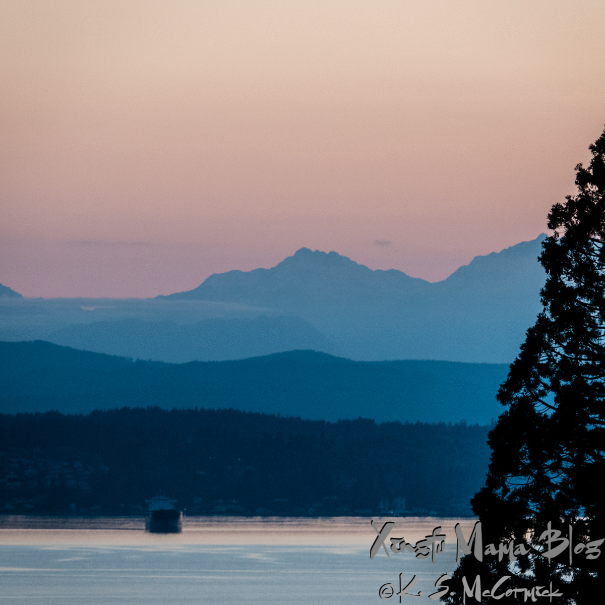 The hills of Kitsap Peninsula and Olympic Mountains appear blue at dusk.