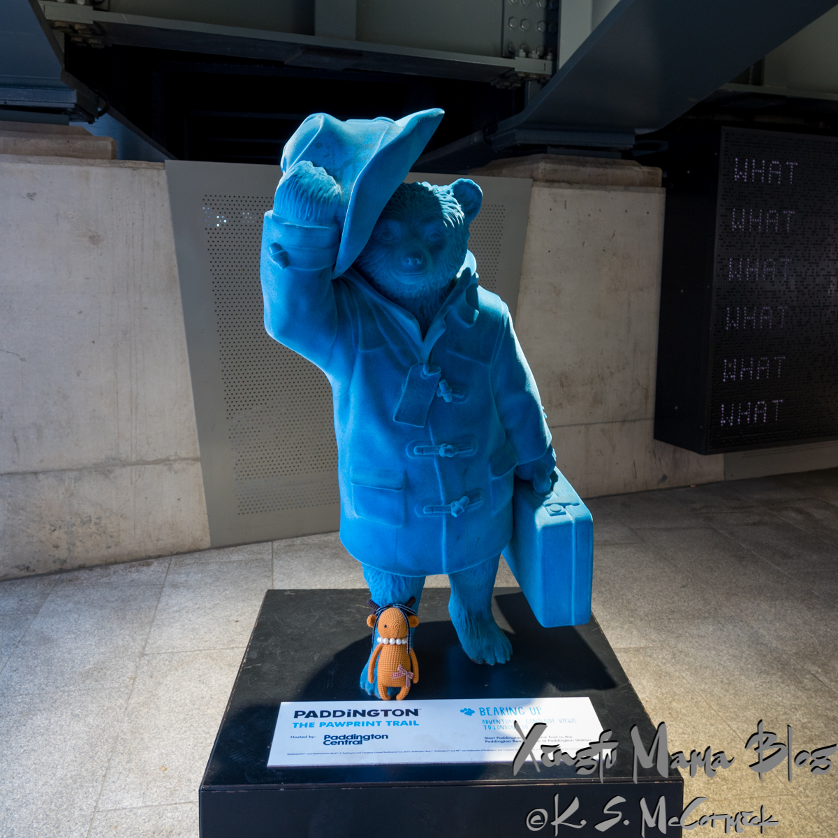 A blue flocked statue of Paddington Bear.