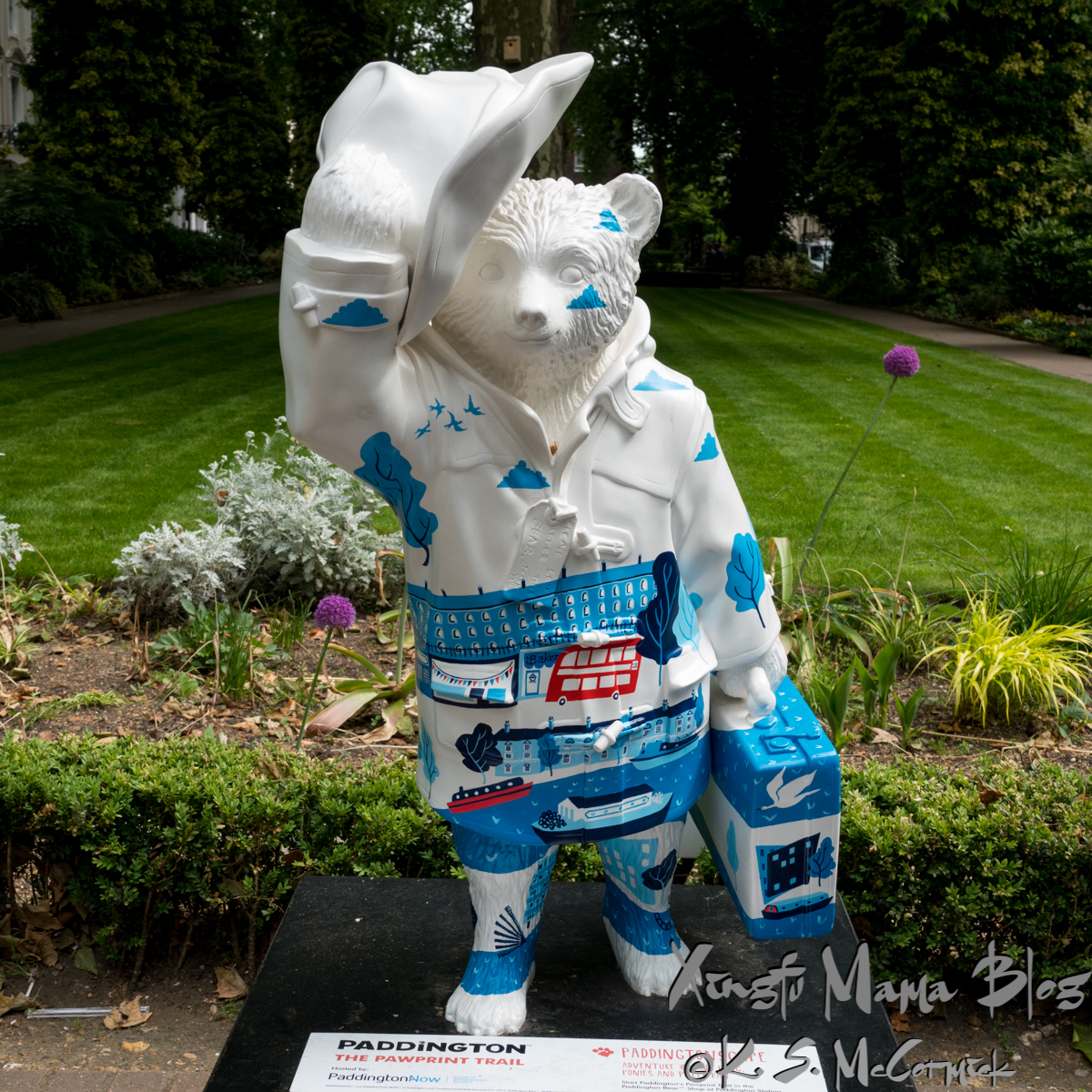 A white Paddinton Bear statue decorated with blue (except for the red double decker bus) London sights.