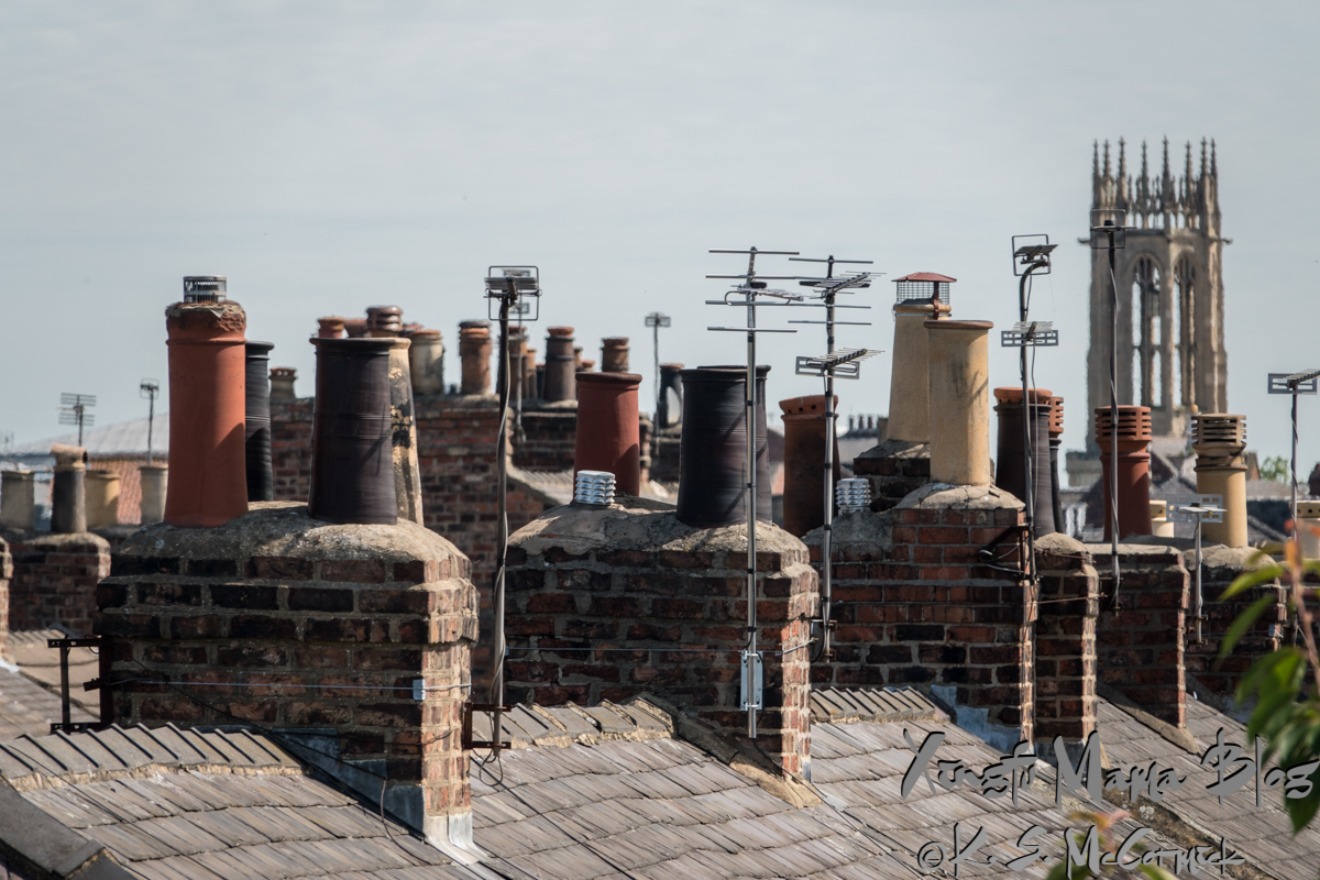 Chimneys, chimney pots and antennas with the tower of a church in the background, York, England.