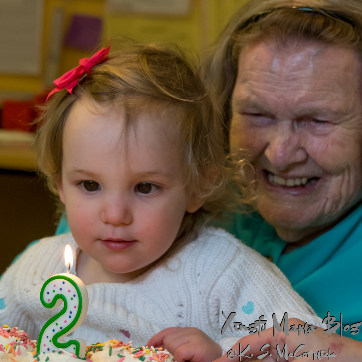 A two year old and 95 year old looking at a #2 birthday candle.