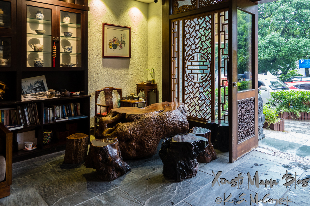 "A solid wood tea table and ""chairs"" made of sliced tree crosssections beside an elegant Chinese screen and door. This is the lobby of the Aroma Tea House in Guilin, China."