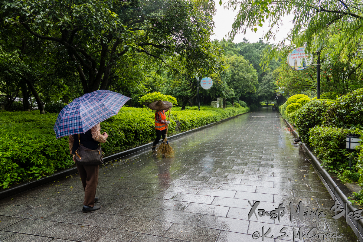 A woman with an umbrella walking on a wet walkway paved with stone being swept by an orange vested worker wearing a broad brimmed woven bamboo hat, in Guilin, China.