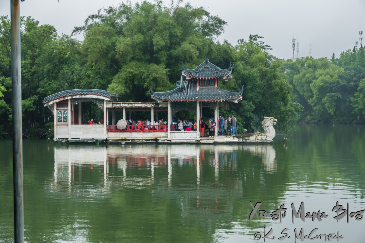 A group of people singing in a floating pavilion with a dragon head on Rong Lake in Guilin, China.