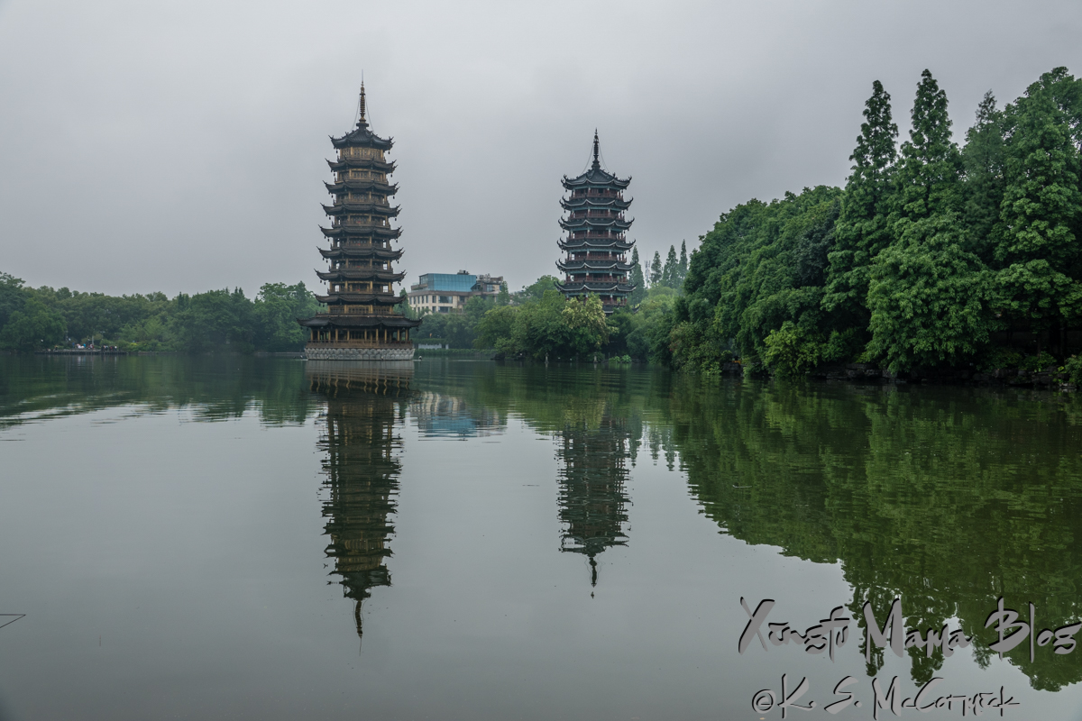 The sun and moon pagodas on Rong Lake in Guilin, China, on a gray, rainy day.