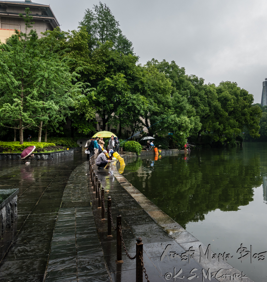 People with umbrellas fishing in the lake in Guilin, China.