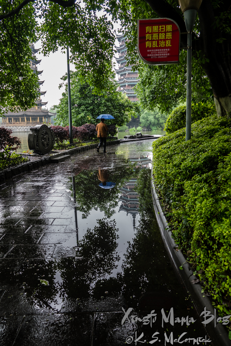 A large puddle reflects the moon pagoda and a walker with an umbrella, in Guilin, China.