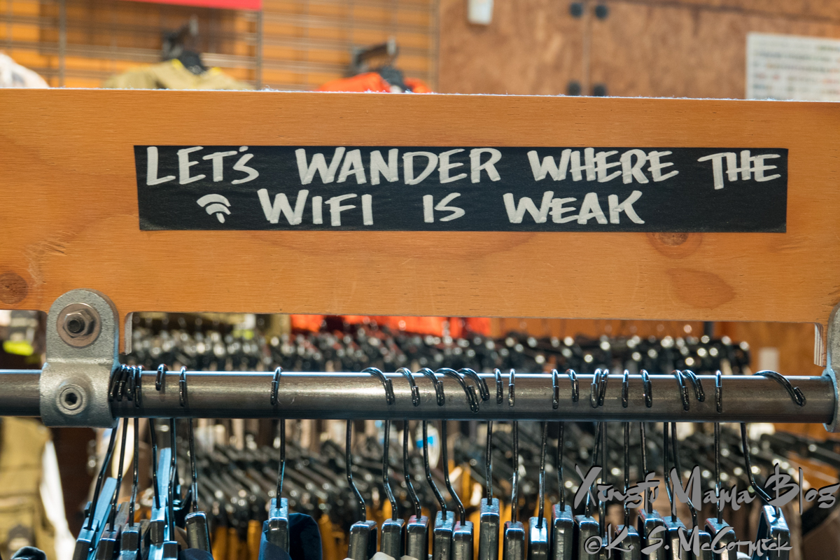 "Sign in REI's flagship store in Seattle, saying ""Let's wander where the wifi is weak""."