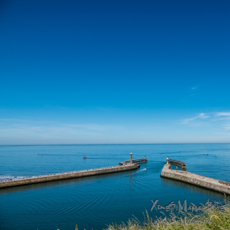 Deep blue sky and water accent the piers at the entrance to Whitby Bay, in Yourkshire, England